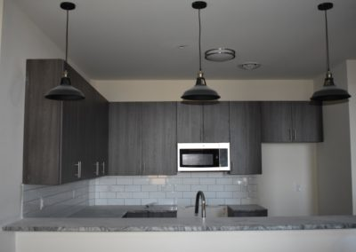 Dark cabinetry and hanging lights in Wyomissing apartment kitchen